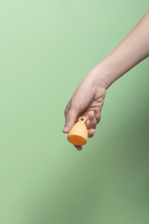 Cocmau Menstrual Cup in Sunshine Yellow held in a hand
